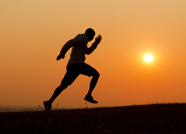 Sunset silhouette of a man running uphill