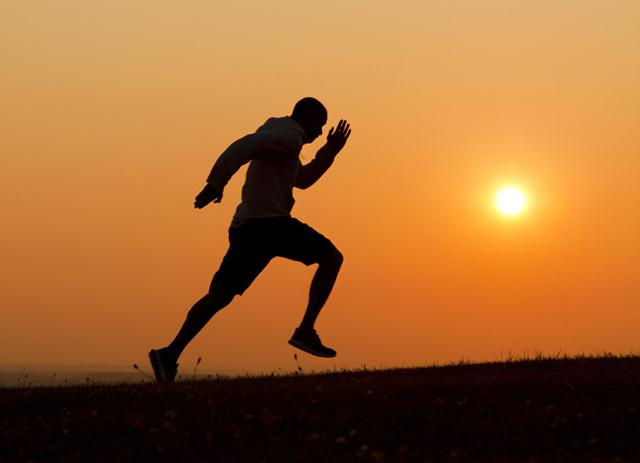 Sunset silhouette of a man running uphill