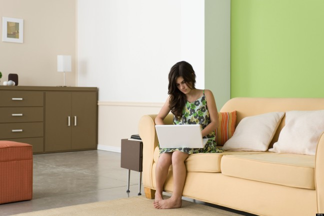 Teenage girl using laptop in living room